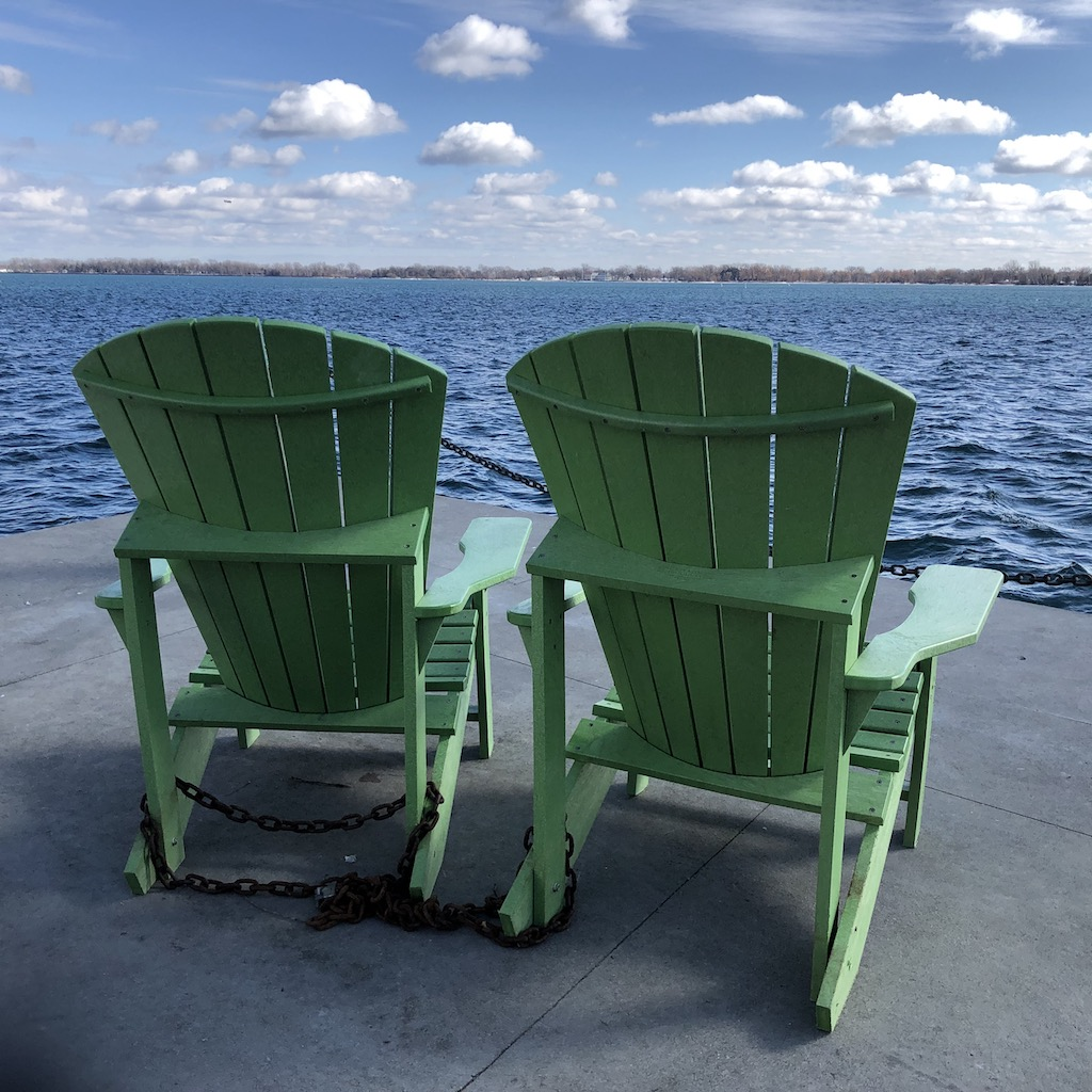 Green chairs by the lake.