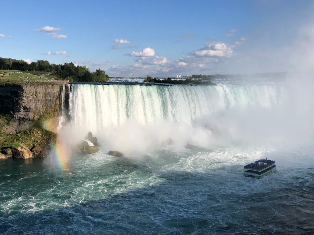 A small rainbow appeared to the left while the Maid of the Mist boat approached Horseshoe Falls.